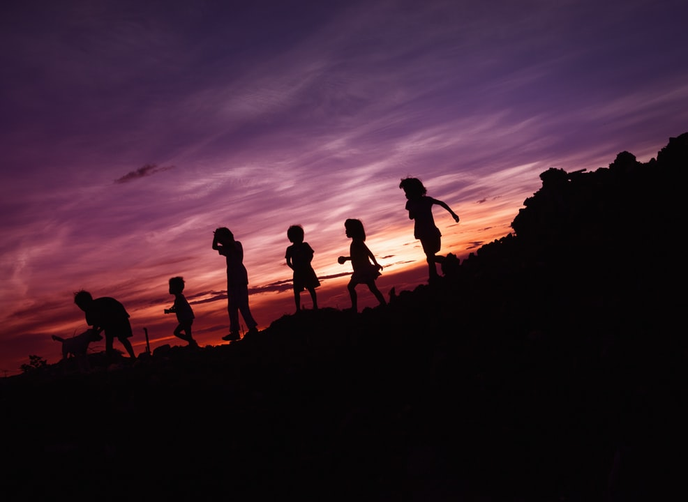 Kids playing with their dog during sunset. Photo by Rene Bernal on Unsplash